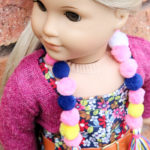 Make a pom pom scarf for dolls.